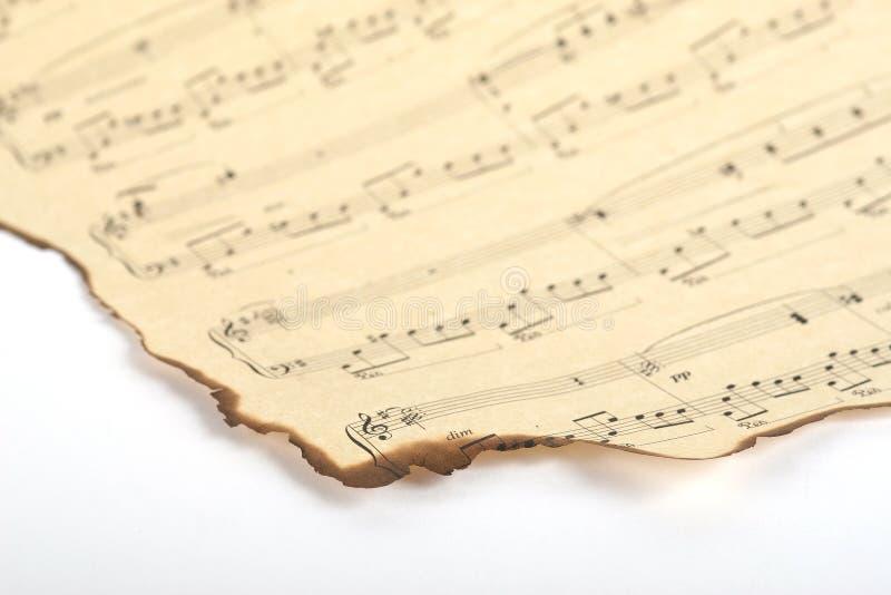Del av det gamla brända musikarket på pappers- och vit bakgrund för tappning royaltyfria foton