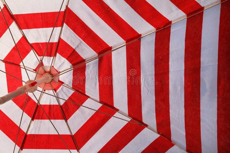 Del av det röda och vita solparaplyet för att solbada och skydd av solstrålar, closeup Textur material, modell, bakgrund fotografering för bildbyråer