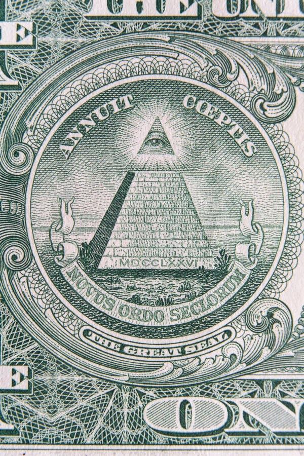 Del av en dollaranmärkning med det toppna makroskottet för stor skyddsremsa Öga av försyn eller all-att se ögontecknet, detalj i  royaltyfria foton
