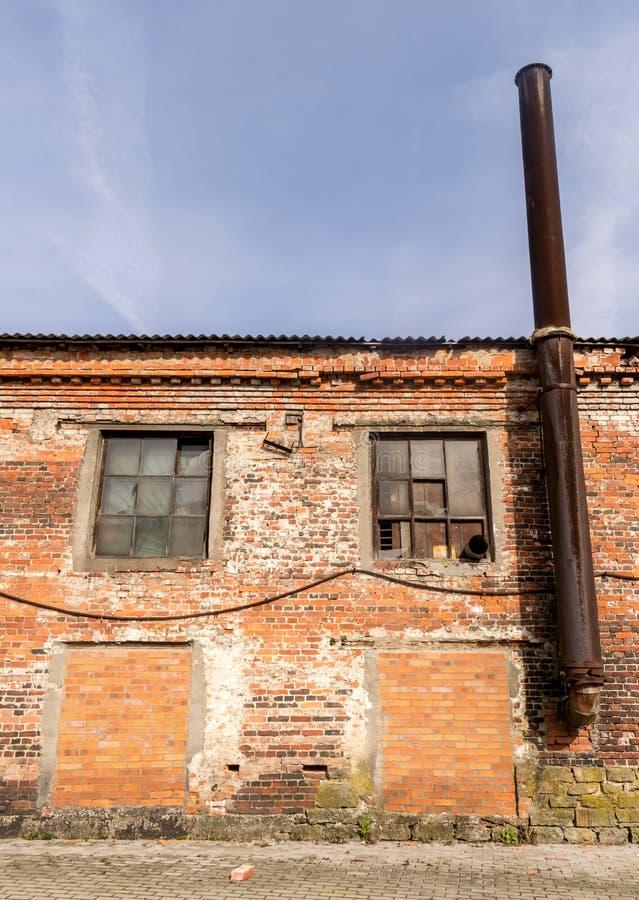 Del av en gammal fabrik för röd tegelsten med en gammal rostig lampglas royaltyfri fotografi