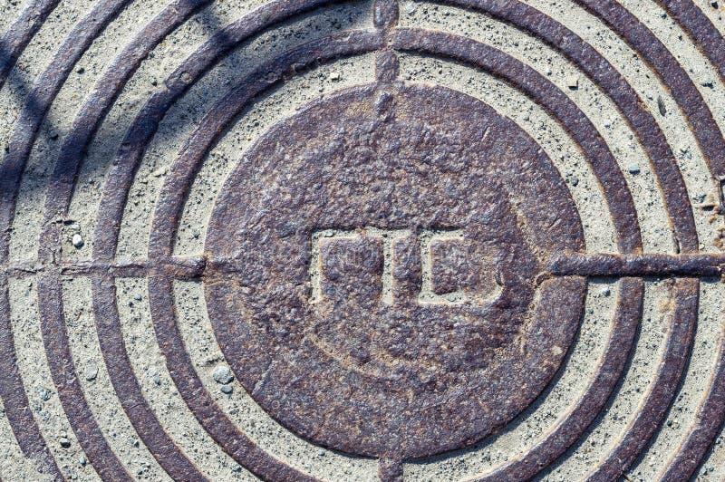 Del av en järn- manhål för kloak med inskriften i ryss 'GTS ', royaltyfri foto