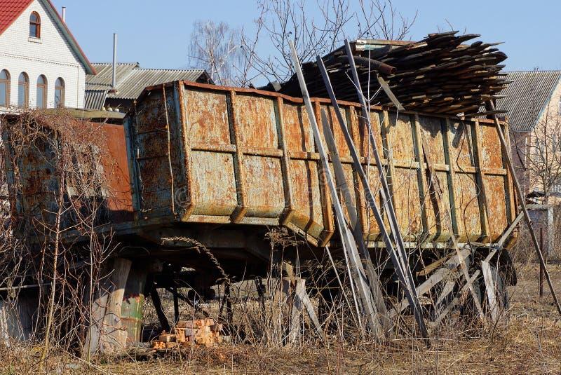 Del av en lastbil med en stor rostig järnkropp i gatan med avskräde arkivfoto
