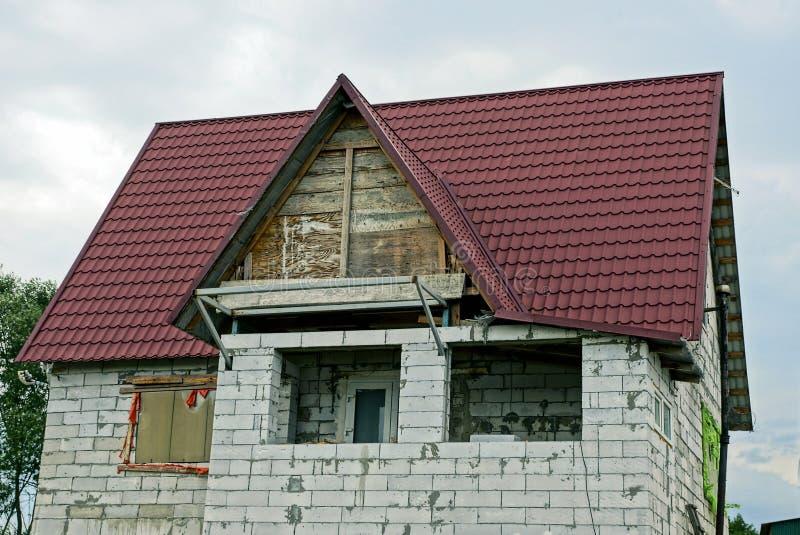 Del av ett oavslutat hus av grå tegelsten med en loft och ett tak under röda tegelplattor arkivbilder