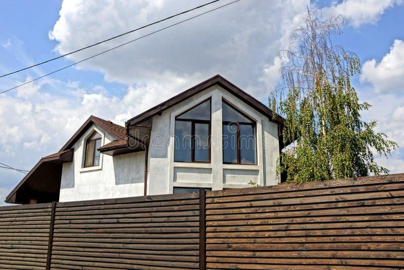 Del av ett vitt hus med ett fönster bak ett brunt trästaket mot himlen och molnen royaltyfri fotografi