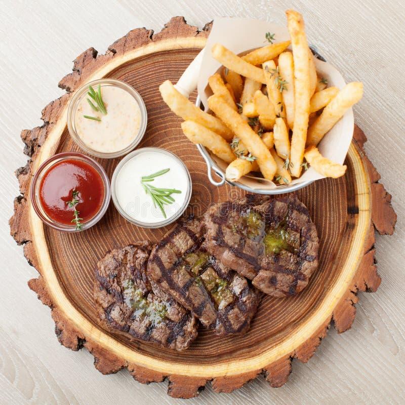 Del av mignonen för BBQ-nötköttfilet med såser och stekte potatisar royaltyfria bilder