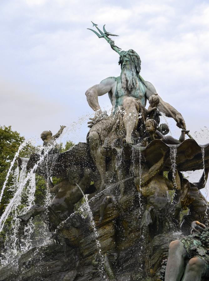 Del av Neptunspringbrunnen mot en blå himmel med moln i t royaltyfria foton
