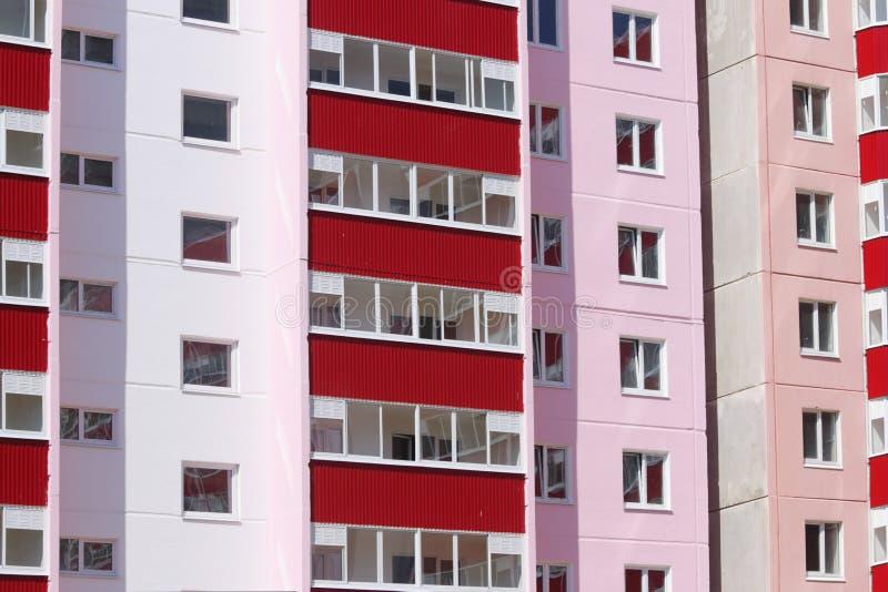 Del av rosa bostads- byggnad med röda balkonger och dou royaltyfri foto