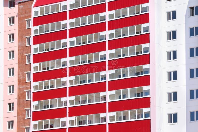 Del av rosa bostads- byggnad med röda balkonger på solen arkivfoto