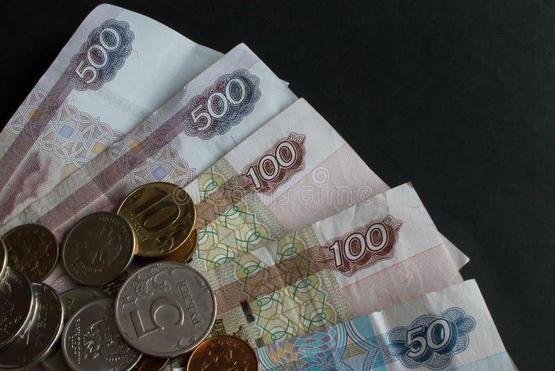 Del av ryska pappers- pengar och en spridning av metallmynt av olika valörer på dem närbild på en svart bakgrund arkivfoto