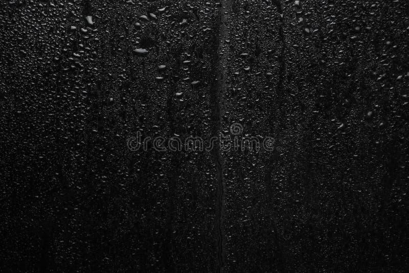 Del av serie Bakgrundsfotoet av regn tappar på mörkt exponeringsglas, olikt format: liten medel och stort royaltyfria bilder