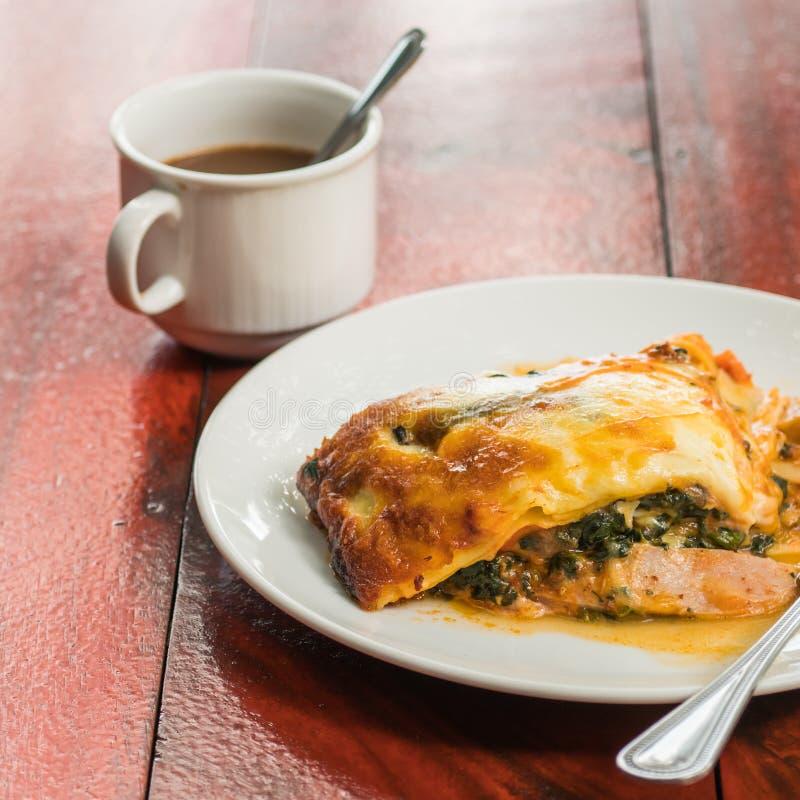 Del av smakliga lasagner med en kopp kaffe arkivfoto