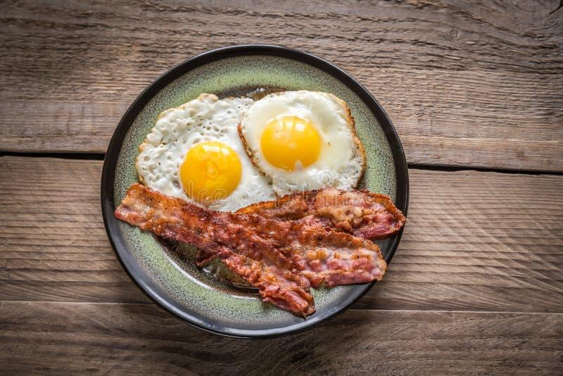 Del av stekte ägg med bacon arkivfoto