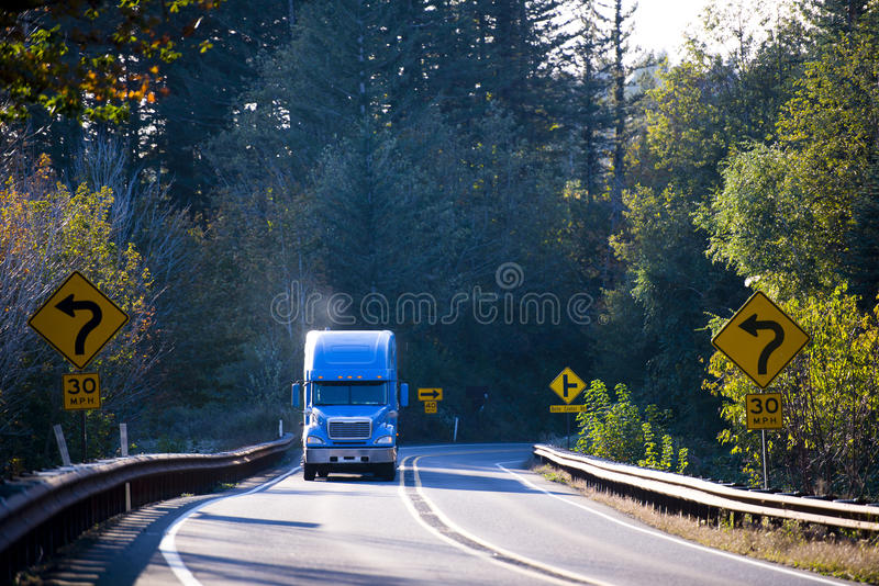 Del azul camión semi en el camino soleado del verde de la bobina con los árboles imágenes de archivo libres de regalías