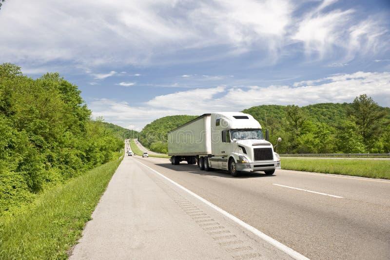 Del blanco camión semi en la carretera en primavera imagen de archivo