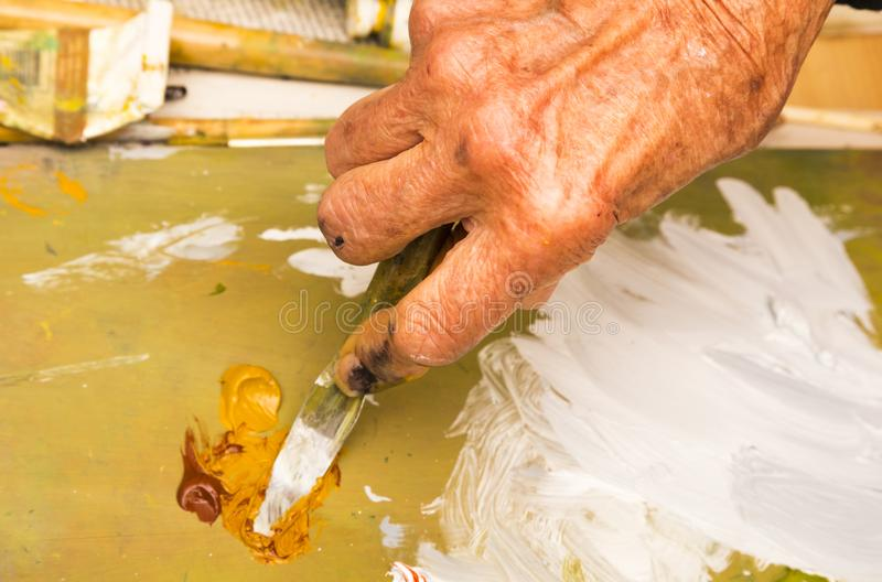Del cierre mano para arriba - de la pintura de aceite de mezcla de la mujer mayor con el cuchillo de paleta foto de archivo