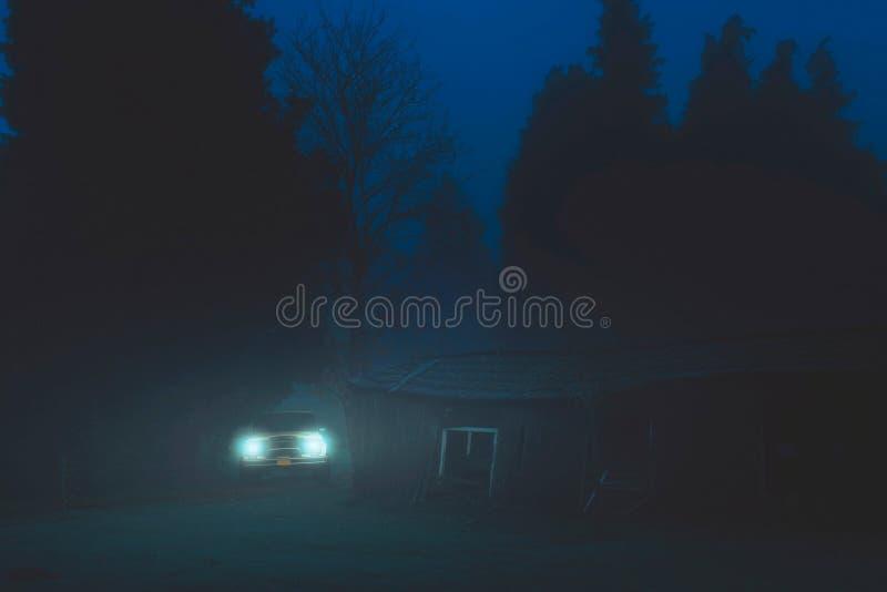 Del coche del camino con las linternas encendido en bosque brumoso cerca del granero viejo fotos de archivo libres de regalías