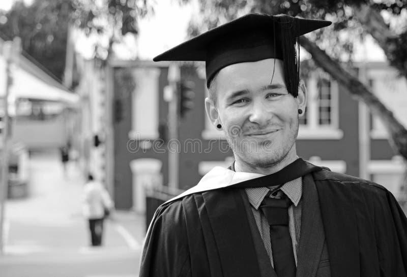 Del hombre día de graduación nervioso emocionado joven uni en casquillo fotografía de archivo
