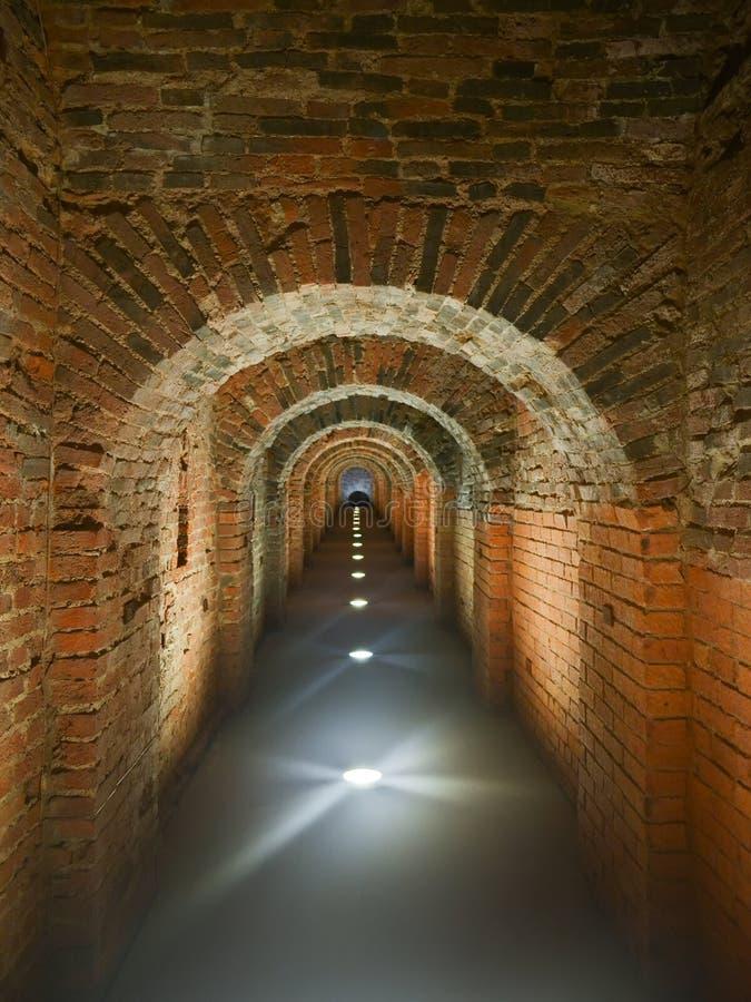 Del ladrillo pasillo arqueado místico oscuro de largo iluminado en el piso imagenes de archivo
