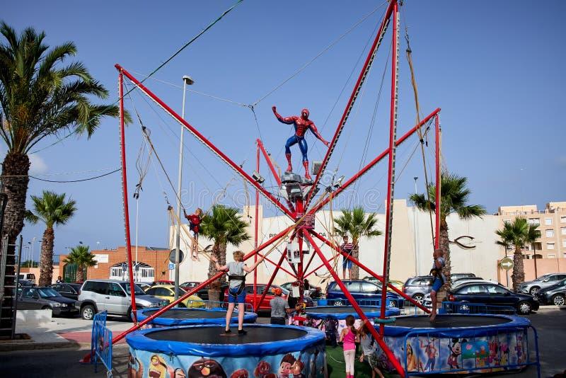 Del Segura de Guardamar, Espanha - 26 de junho de 2016: As crianças no parque de diversões saltam altamente no trampolim imagens de stock