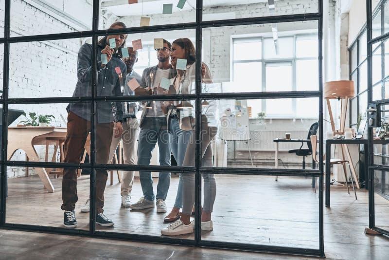 Dela affärsidéer Full längd av ungt modernt folk i sm arkivfoton