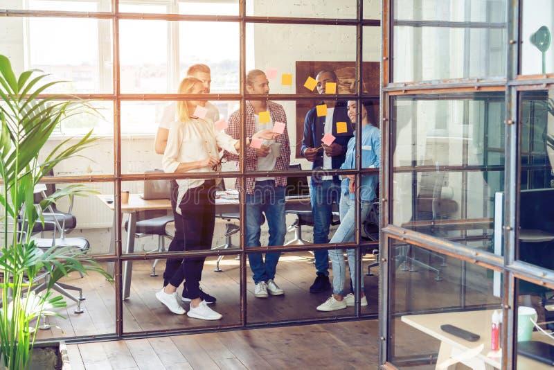 Dela affärsidéer Full längd av ungt modernt folk i smarta tillfälliga kläder genom att använda bindemedelanmärkningar, medan stå fotografering för bildbyråer