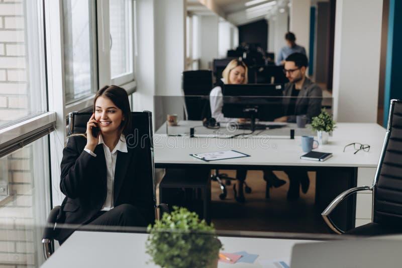 Dela bra ekonominyheter Attraktiv ung kvinna som talar på mobiltelefonen och ler, medan sitta på hennes arbetsplats in arkivbilder