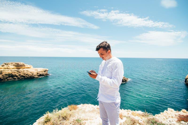 Dela mina sinnesrörelser Den lyckliga unga mannen skriver meddelandet på mobiltelefonen på havkusten royaltyfri foto