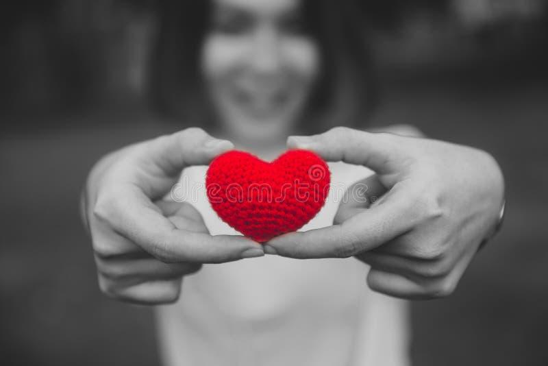 Dela röd färg för förälskelse och för hjärta på kvinnahanden i dag för valentin` s arkivfoton