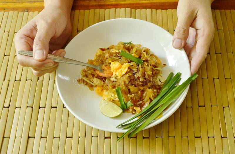 Dela sig att kamma hem stekte risnudlar för blocket thailändsk uppståndelse från plattan arkivfoto