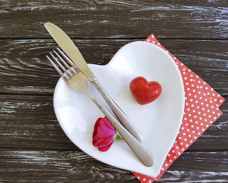 Dela sig, baktala, plätera hjärta, blomma som den rosa kortbegreppsårsdagen firar inbjudanhändelse på träbakgrund royaltyfri foto