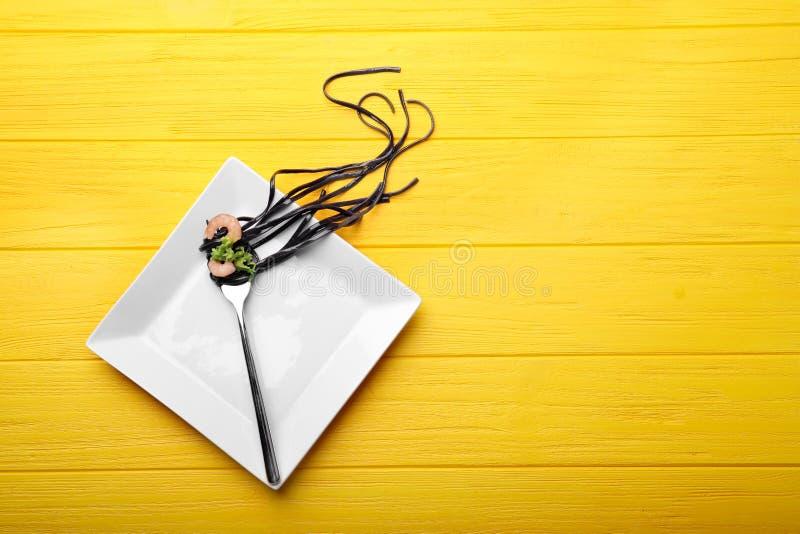 Dela sig med svart pasta och räka på den vita plattan royaltyfri foto