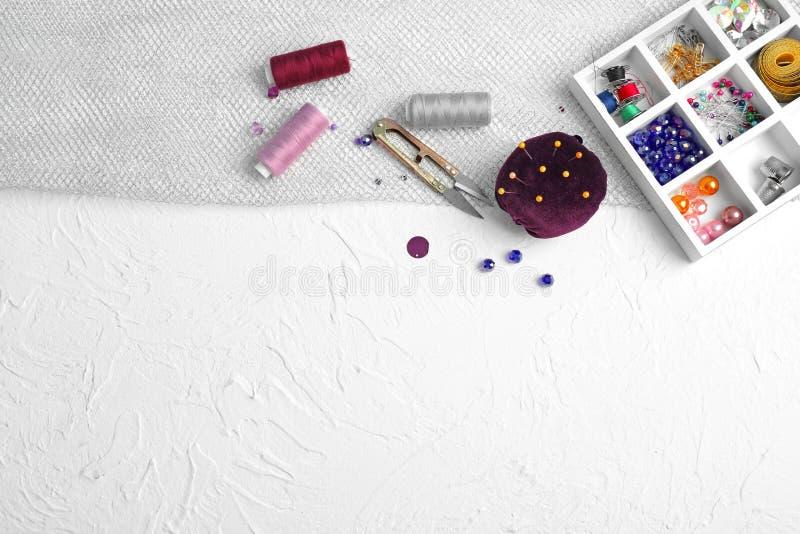 Delad ask med sömnadtillbehör och trådar på vit texturerad bakgrund royaltyfri foto