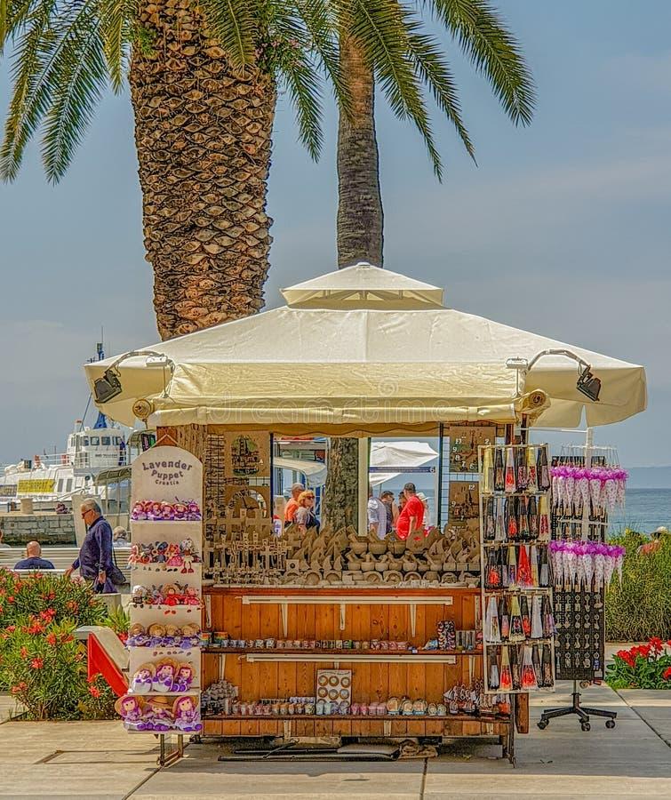 Delad Kroatien - Juni 5, 2019: presentaffär under palmträd i en sydlig semesterortstad vid havet, sommarsightsemester royaltyfria foton