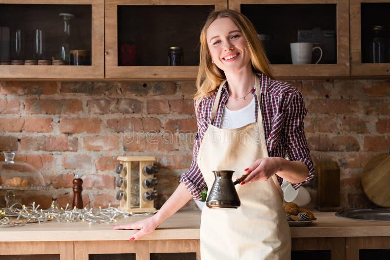 Delantal de la mujer que hace la cocina del hogar de la mañana del café fotos de archivo