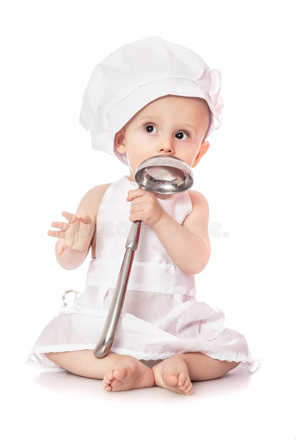 Delantal del cocinero del retrato emocional del bebé y sombrero del cocinero que llevan con la cucharón del metal, aislada en un  fotos de archivo