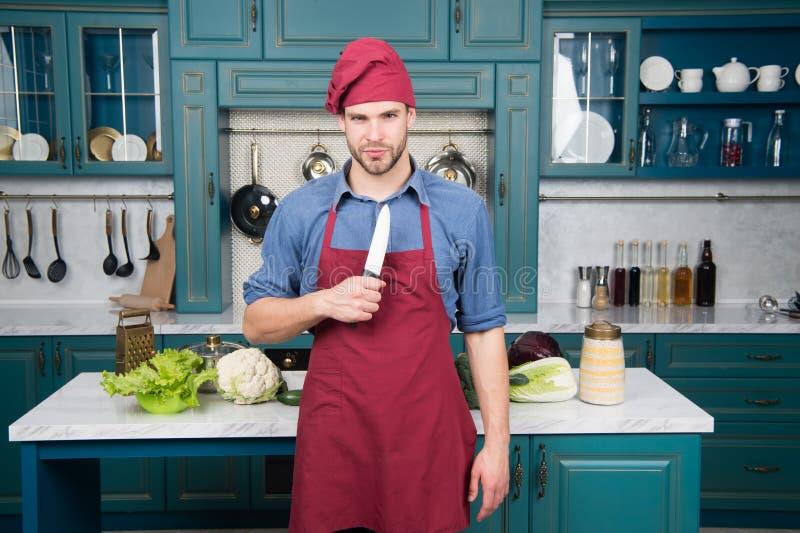 Delantal del desgaste del cocinero del hombre que cocina en cocina Cuchillo de cerámica agudo del uso del hombre Herramienta del  imagen de archivo