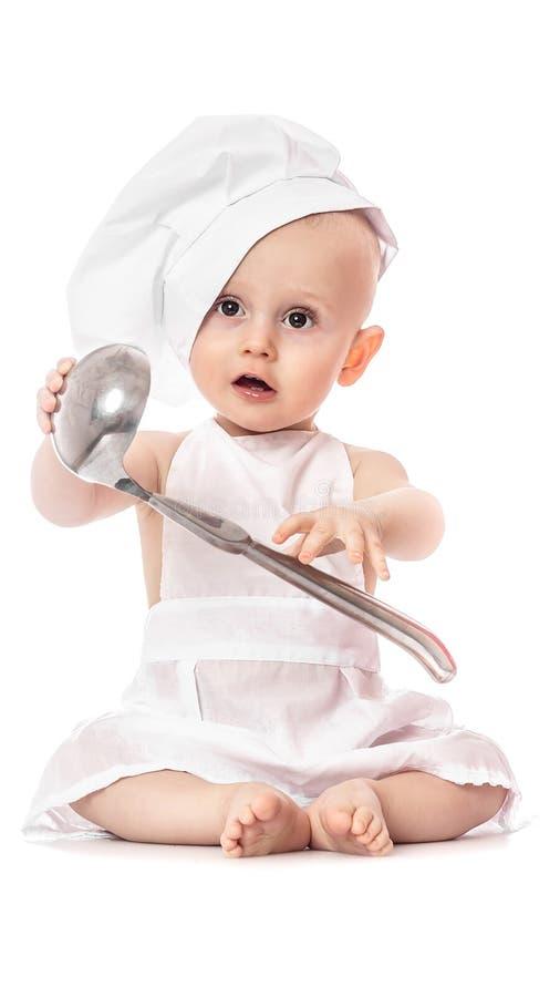 Delantal del retrato adorable del bebé y sombrero del cocinero que llevan con la cucharón del metal, aislada en un fondo blanco C imagen de archivo libre de regalías