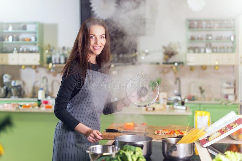 Delantal que lleva de la mujer bastante joven que hace la cena que cocina los espaguetis después de la receta en un libro que se  fotos de archivo libres de regalías
