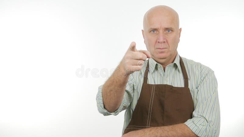 Delantal que lleva de la persona confiada que señala con el finger serio fotografía de archivo