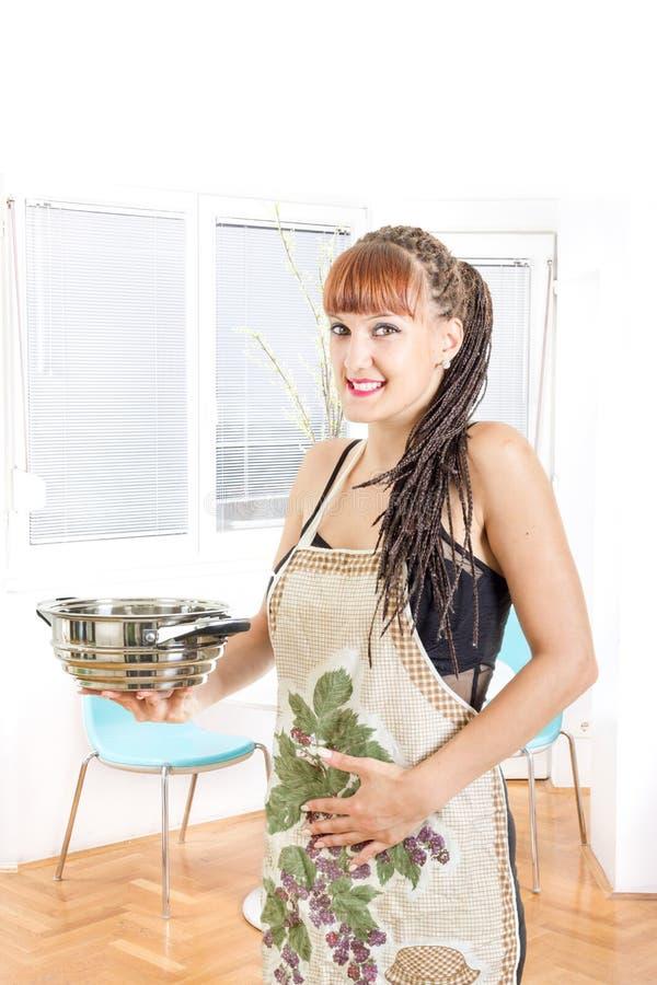 Delantal que lleva del ama de casa embarazada de los jóvenes en la sonrisa de la cocina imagen de archivo
