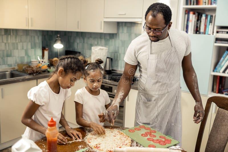Delantal rayado que lleva del padre que ayuda a sus niñas que hacen la pizza imagenes de archivo