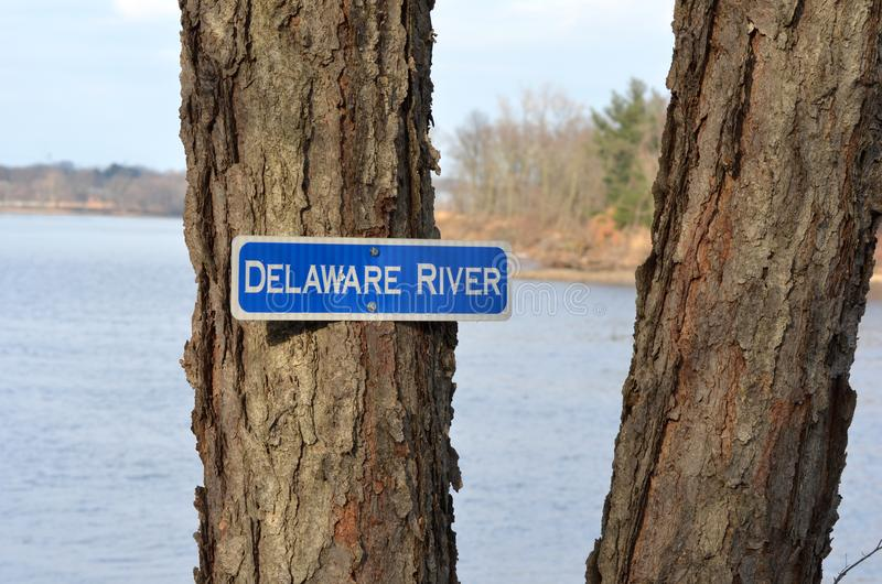 Delaware River. A sign on a tree trunk identifies the body of water behind where the Delaware River flows between Pennsylvania and New Jersey on its way to the royalty free stock image