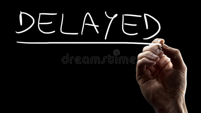 Delayed. Male hand writing word Delayed on black virtual screen stock photo