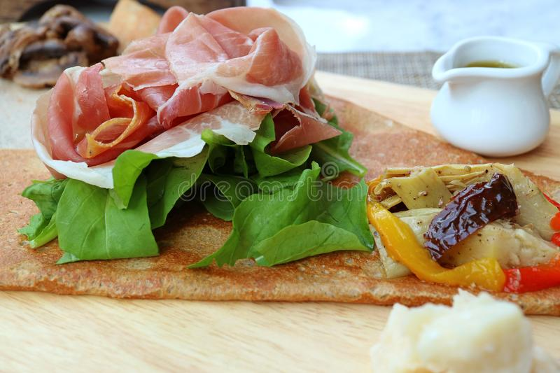 Delectable cold cuts ham with fresh vegetable and cheese of European style Appetizer Crepe stock photos