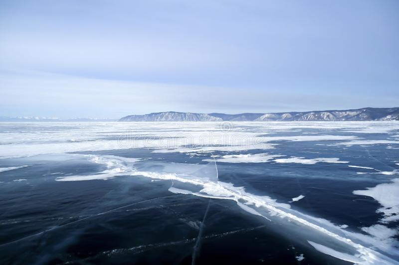 Deep crack in thick dark blue ice on frozen lake stock photo