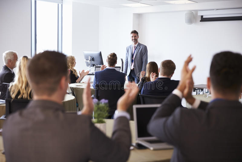 Delegados que aplaudem o homem de negócios Making Presentation imagem de stock