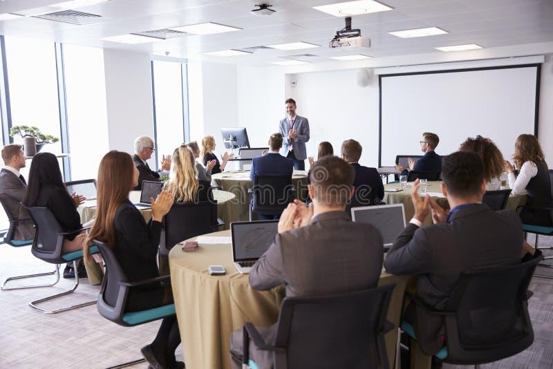 Delegados que aplaudem o homem de negócios Making Presentation fotografia de stock royalty free