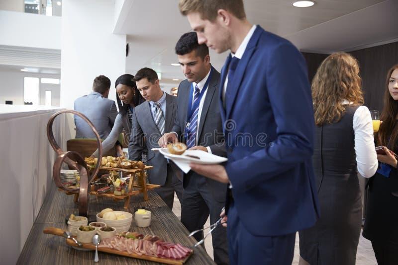 Delegater på lunchbuffé under konferensavbrott royaltyfria bilder