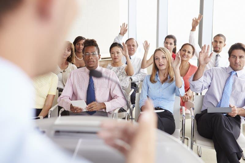 Delegater som frågar fråga på affärskonferensen royaltyfri fotografi