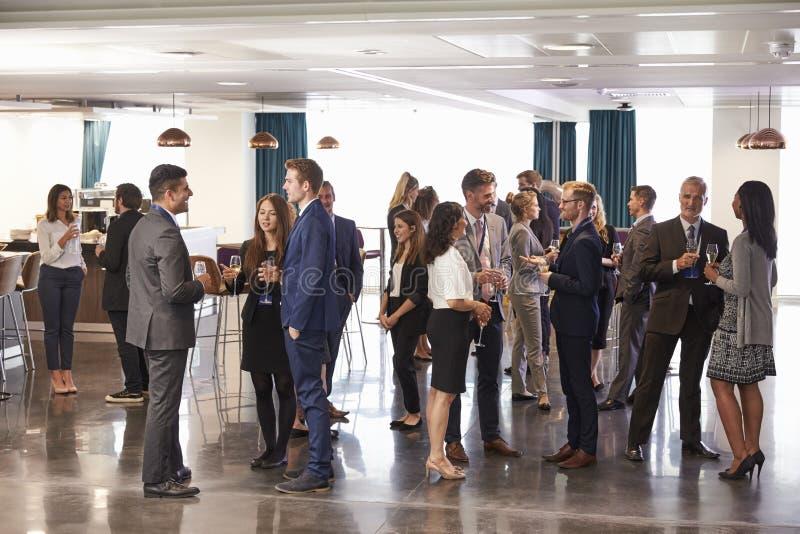 Delegater som knyter kontakt på konferensen, dricker mottagande